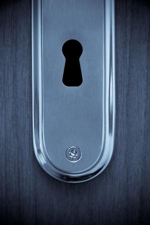 Close-up shot van een sleutelgat. Blauw afgezwakt.