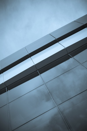Modern building top with cloud reflections on glasses. Toned.