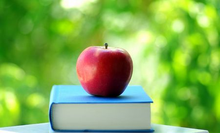 A red apple on a book of blue color