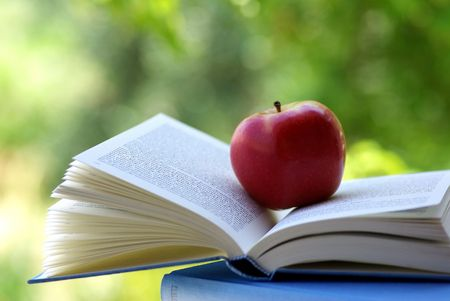 red apples: A red apple on a book of blue color
