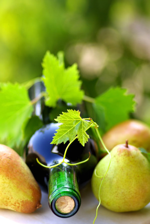 Bottle of wine and fruit with grapevine leves. Stok Fotoğraf