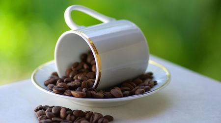 overthrown: Cup overthrown with coffee grains. Stock Photo