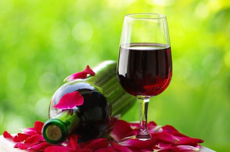 Petals of rose in a glass of red wine. Stock Photo - 2905695