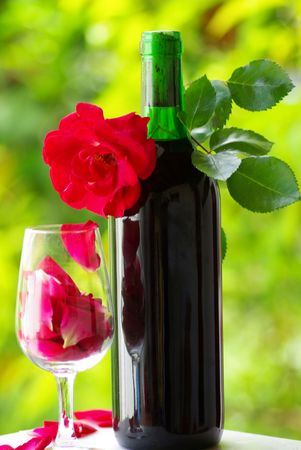 Petals of rose in a glass of red wine. photo