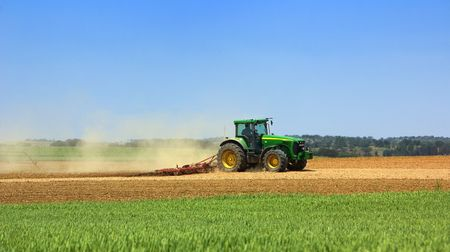 Green tractor working in the field. photo