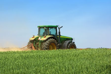 Green tractor working in the field. Stock Photo