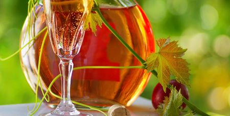 Glass and bottle of Rose wine with green leaf. photo