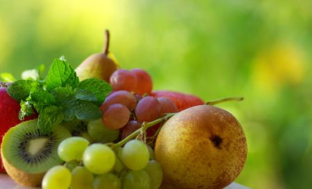 Colored fresh fruits on green background. Stock Photo - 3695096