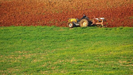 Small tractor cultivating the land. photo