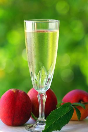 Glass of white wine and red peaches. photo
