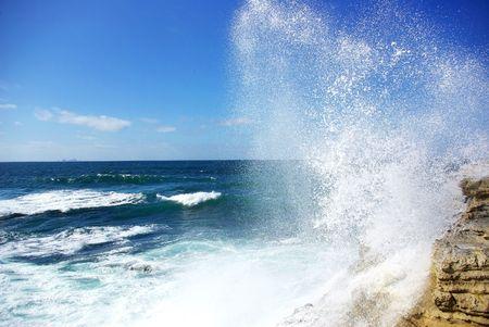 A wave breaks in the rock.