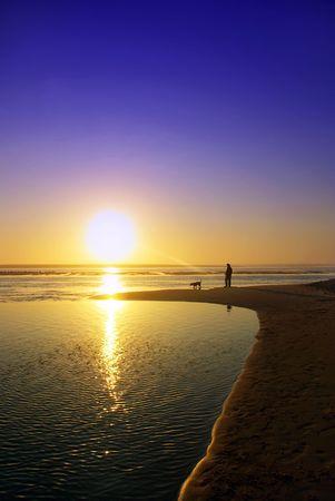 Man and dog at sunset. photo