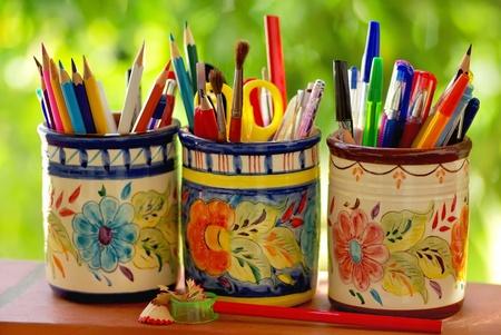 fournitures scolaires: Trois pots, des crayons et des objets scolaires sur un fond vert