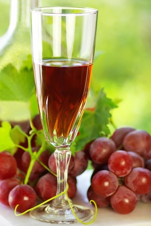 Glass of rose wine and mature grapes. photo