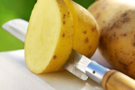 Potato and knife on table  photo