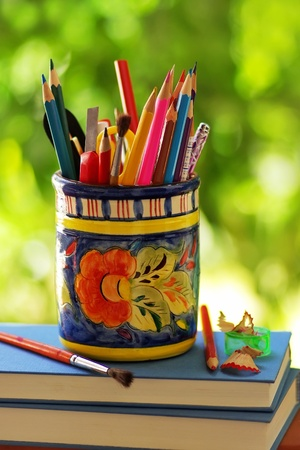 jar, pencils and school objects on a green background photo
