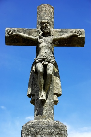 Old cross, and Christ in blue sky. photo