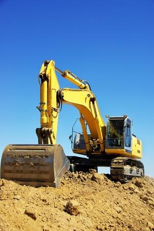 Yellow excavator on a working platform