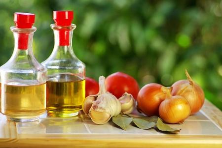vinegar bottle: Oliveoil, vinegar and vegetables. Stock Photo