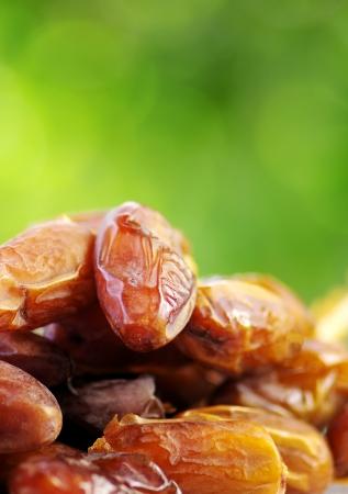 arabian food: Fresh dates isolated on green background Stock Photo