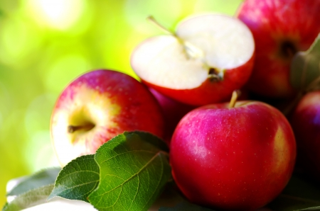 ripe red apples on table, green background photo