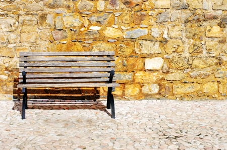 Wood bench against a brick wall  photo