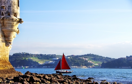 fortification: Red sailboat on Tejo river, Portugal