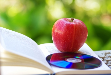 Ripe apple, dvd, and open book  photo