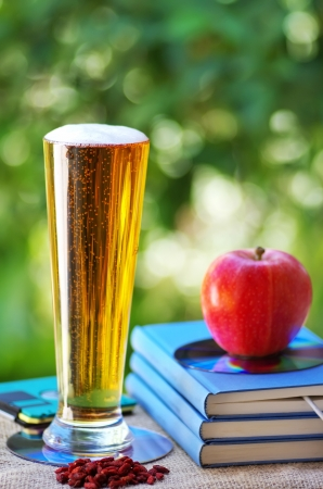 Cold beer and apple on books photo