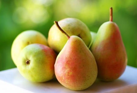 pera: Peras maduras frescas sobre fondo verde Foto de archivo