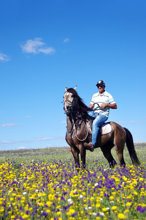 Young man  with his horse on field