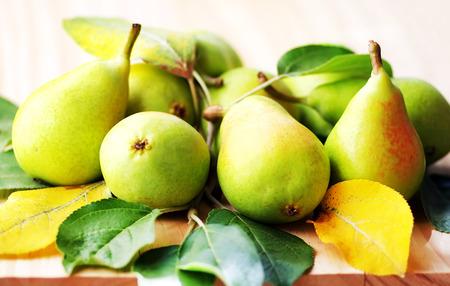 pera: peras con hojas en la mesa de madera Foto de archivo