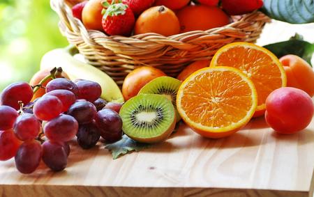basketful: half orange, sliced kiwi, other fruits in the basket Stock Photo