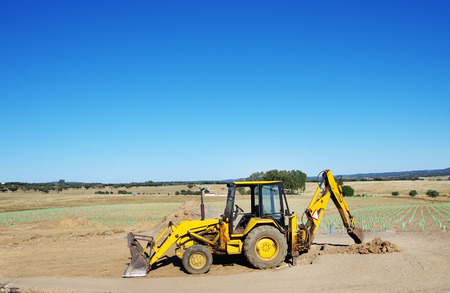 earthmover: Yellow excavator on agriculture field Stock Photo