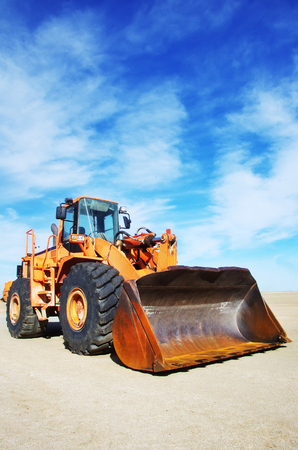 Orange loader bulldozer with cloud sky Stock Photo