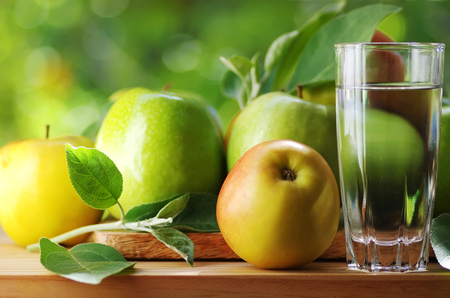 fresh ripe apples and glass of water