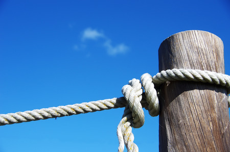 White rope tied with knot to wooden pole Stok Fotoğraf