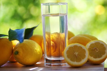 Water of glass with lemon isolated on the green background