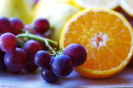 grapes and slices of orange fruit Standard-Bild - 131221398