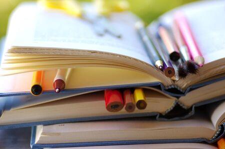 pens and pencils in open books Standard-Bild - 131221431
