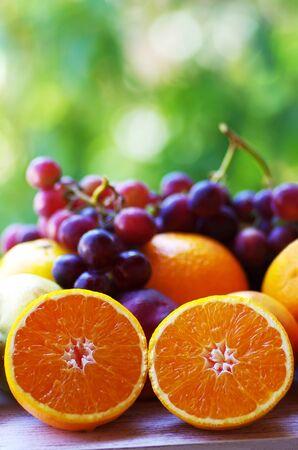 sliced oranges and grapes, green background Standard-Bild - 131221432