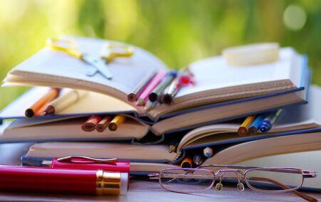 pens and pencils in open books Standard-Bild - 131221442
