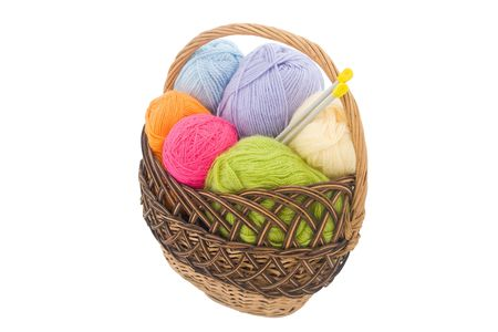 colored wool clews with needles in wicker basket  photo