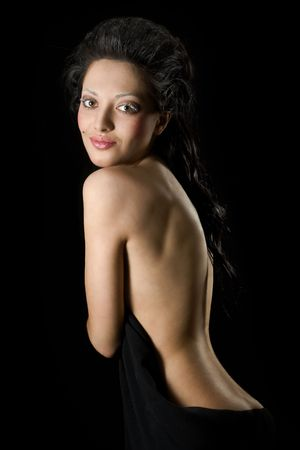 woman back of head: Portrait of  beautiful woman.Naked back. Low key. Looking At Camera. Full lips