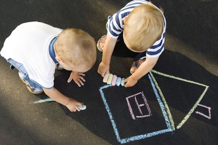 squatting down: two boys drawing house on asphalt holding chalks Stock Photo