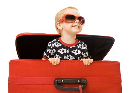 sun shades: Little kid in sunglasses looking out red suitcase. Isolated on white Stock Photo
