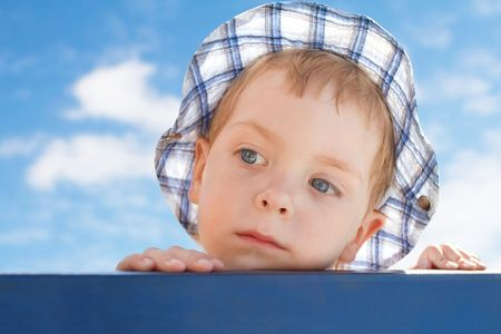 sad  little boy in hat looking away on sky background  photo