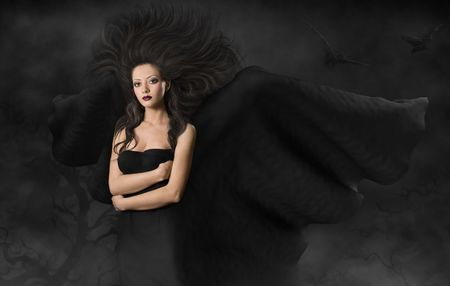 Dark angel. Beautiful gothic style woman with wings standing in fog at black night photo