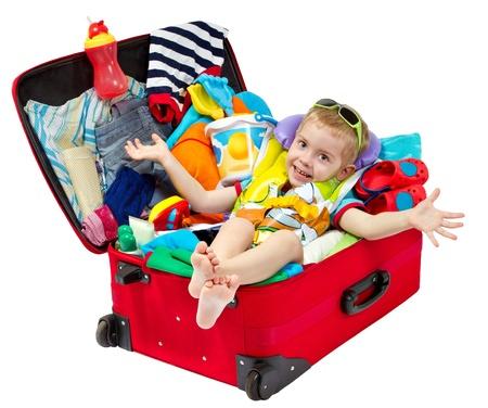 maletas de viaje: Little kid en viajes maleta roja. Bolsas para vacaciones en el mar resort. Efectos personales: sombrero, crema, toalla. Aislados en blanco Foto de archivo