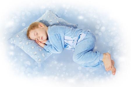 pillows: cute little child sleeping on pillow. Magic background